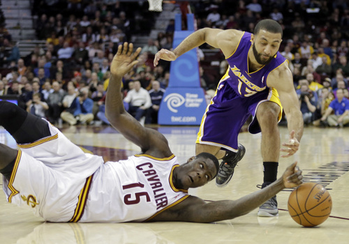 Cleveland Cavaliers' Anthony Bennett (15) bats a loose ball away from Los Angeles Lakers' Kendall Marshall in the fourth quarter of an NBA basketball game on Wednesday, Feb. 5, 2014, in Cleveland. The Lakers won 119-108. (AP Photo/Mark Duncan)