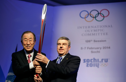 United Nations Secretary-General Ban Ki-moon, left, is presented with an Olympic torch by International Olympic Committee President Thomas Bach, right, after Ban addressed the IOC's general assembly ahead of the upcoming 2014 Winter Olympics, Thursday, Feb. 6, 2014, in Sochi, Russia. It was the first time a U.N. secretary-general delivered a keynote address to the IOC's general assembly. (AP Photo/David Goldman)