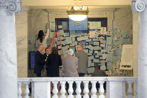 Al Hartmann  |  The Salt Lake Tribune  People stop by the entrance doors to the Senate at the Utah State Capitol Monday morning February 3, 2014, to see it plastered with hundreds of messages to pass SB100. SB100 is sponsored by Senator Stephen Urquhart, R-St. George, left. The bill modifies the Utah Antidiscrimination Act and Utah Fair Housing Act to address discrimination on the basis of sexual orientation and gender identiity.