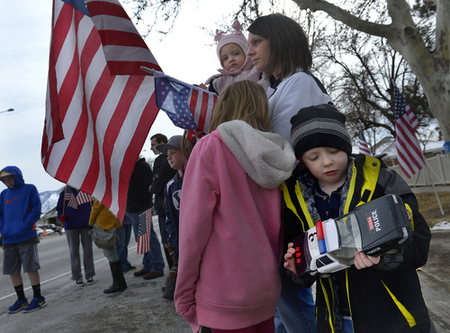 Scott Sommerdorf   |  The Salt Lake Tribune Five-year-old Kellen Mills, right, held his toy police car as he and the Mills family of Spanish Fork waited for Utah County Sheriff's Sgt. Cory Wride's procession to pass on Main Street in Spanish Fork, Wednesday, Feb. 5, 2014.