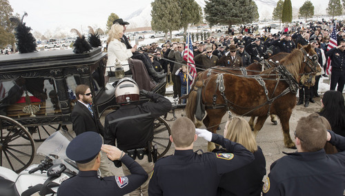 Steve Griffin  |  The Salt Lake Tribune   A horse drawn hearse delivers the body of slain Utah County Sheriff's Sgt. Cory Wride during interment services at the Spanish Fork Cemetery, in Spanish Fork, Utah Wednesday, February 5, 2014. Wride's wife, Nanette Wride, center, road with the hearse.
