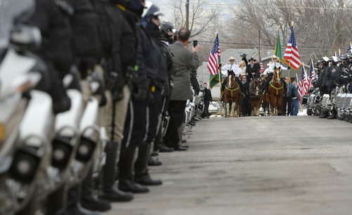 Steve Griffin  |  The Salt Lake Tribune   A horse drawn hearse delivers the body of slain Utah County Sheriff's Sgt. Cory Wride during interment services at the Spanish Fork Cemetery, in Spanish Fork, Utah Wednesday, February 5, 2014. Wride's wife, Nanette Wride, road with the hearse.
