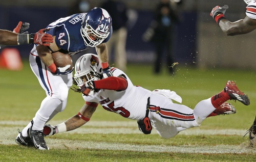 Louisville safety Calvin Pryor, right, dives as he tries to tackle Connecticut running back Max DeLorenzo during the first quarter of an NCAA college football game, in East Hartford, Conn., Friday, Nov. 8, 2013. (AP Photo/Charles Krupa)