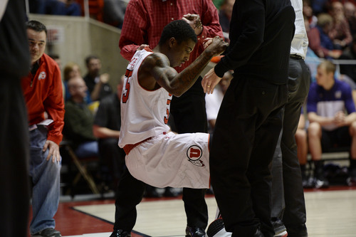 Francisco Kjolseth  |  The Salt Lake Tribune Utah Utes guard Delon Wright (55) gets helped up after taking a shot from Washington to his eye in game action at the Huntsman Center on the University of Utah campus on Thursday, Feb. 6, 2014.