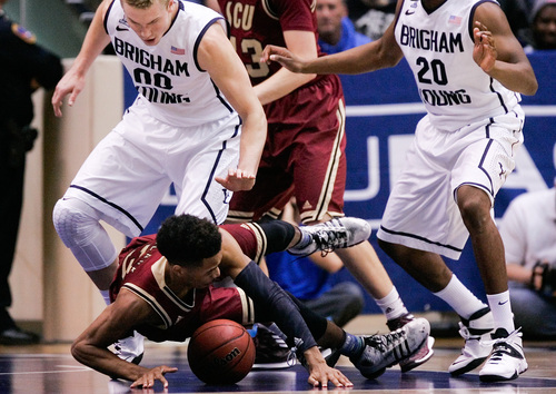 Santa Clara's Brandon Clark, bottom, tumbles after being fouled by BYU's Eric Mika, left, during the NCAA men's basketball game between BYU and Santa Clara at the Marriott Center in Provo, Utah on Thursday, Feb. 6, 2014.  (AP Photo/The Daily Herald, Spenser Heaps)