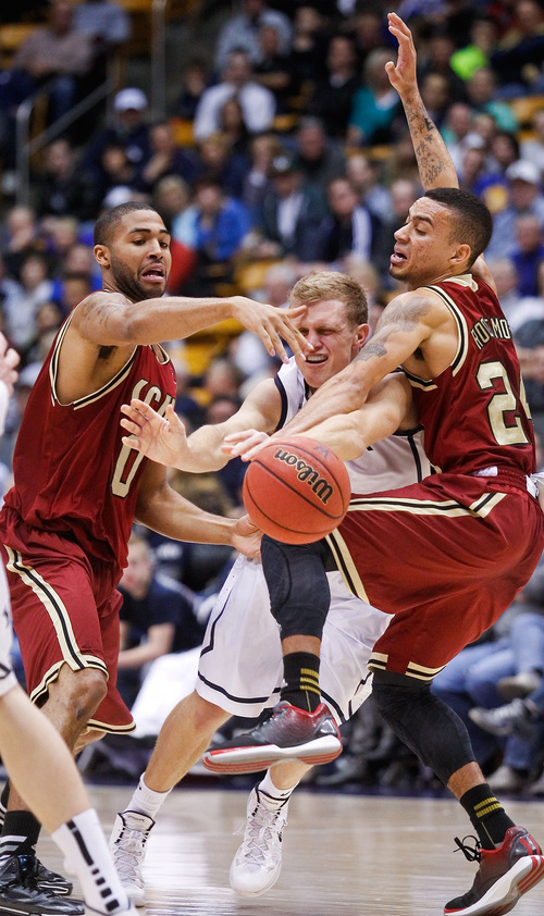 BUY's Tyler Haws, center, looses the ball as he tries to break through Santa Clara's Jerry Brown, left, and Evan Roquemore, right, during the NCAA men's basketball game between BYU and Santa Clara at the Marriott Center in Provo, Utah on Thursday, Feb. 6, 2014. (AP Photo/The Daily Herald, Spenser Heaps)