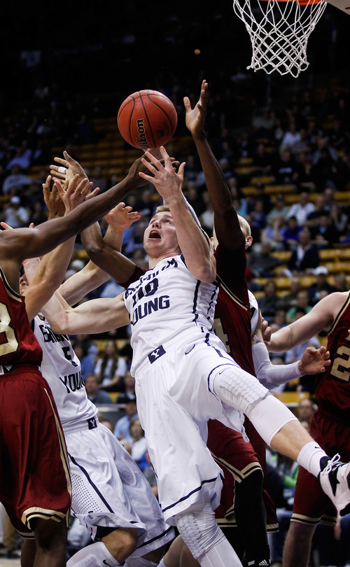 BYU's Eric Mika, center, tries to pull in a rebound during the NCAA men's basketball game between BYU and Santa Clara at the Marriott Center in Provo, Utah on Thursday, Feb. 6, 2014. (AP Photo/The Daily Herald, Spenser Heaps)