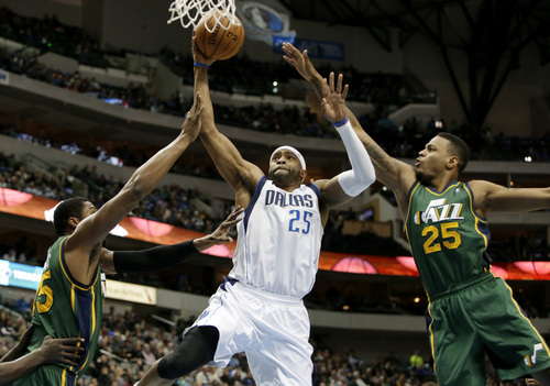 Dallas Mavericks' Vince Carter (25) goes up for a shot between Utah Jazz's Derrick Favors, left, and Brandon Rush (25) in the first half of an NBA basketball game, Friday, Feb. 7, 2014, in Dallas. (AP Photo/Tony Gutierrez)