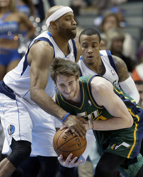 Dallas Mavericks' Vince Carter, left, and Monta Ellis attempt to strip the ball away from Utah Jazz's Gordon Hayward, right, in the first half of an NBA basketball game, Friday, Feb. 7, 2014, in Dallas. (AP Photo/Tony Gutierrez)