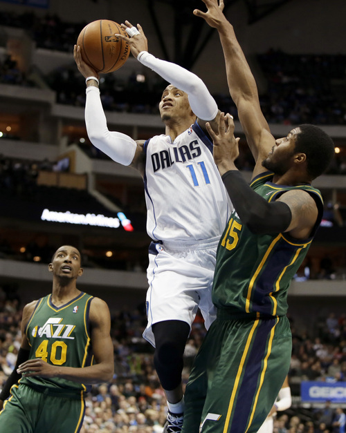 Dallas Mavericks' Monta Ellis (11) goes up for a shot against Utah Jazz's Derrick Favors (15) as Jeremy Evans (40) watch in the first half of an NBA basketball game, Friday, Feb. 7, 2014, in Dallas. (AP Photo/Tony Gutierrez)