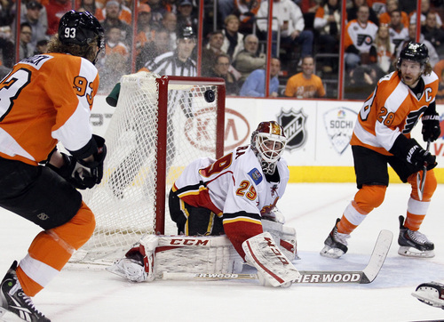 Philadelphia Flyers' Jakub Voracek, left, and Calgary Flames goalie Reto Berra, center, eye the puck Berra deflected that was a pass intended for Claude Giroux, right, during the second period of an NHL hockey game, Saturday, Feb. 8, 2014, in Philadelphia. The Flyers won 2-1.  (AP Photo/Tom Mihalek)