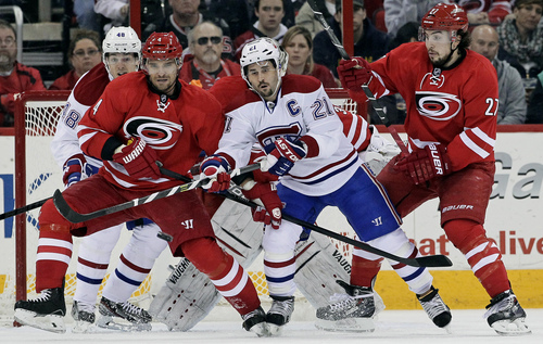 Carolina Hurricanes' Andrej Sekera (4), of Slovakia, and Justin Faulk (27) keep an eye on the puck with Montreal Canadiens' Daniel Briere (48) and Brian Gionta (21) during the second period of an NHL hockey game in Raleigh, N.C., Saturday, Feb. 8, 2014. Montreal won 4-1. (AP Photo/Gerry Broome)