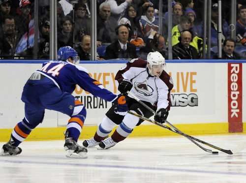 Colorado Avalanche's Matt Duchene, right, controls the puck against New York Islanders' Calvin de Haan (44) in the third period of an NHL hockey game on Saturday, Feb. 8, 2014, in Uniondale, N.Y. Duchene scored two goals during the Avalanche's 4-2 win. (AP Photo/Kathy Kmonicek)