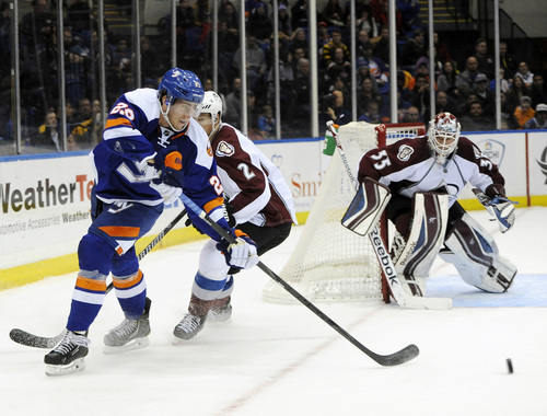 New York Islanders' Brock Nelson (29) drives the puck away from Colorado Avalanche's Nick Holden (2) as goalie Jean-Sebastien Giguere (35) defends the net in the second period of an NHL hockey game on Saturday, Feb. 8, 2014, in Uniondale, N.Y. The Avalanche won 4-2. (AP Photo/Kathy Kmonicek)