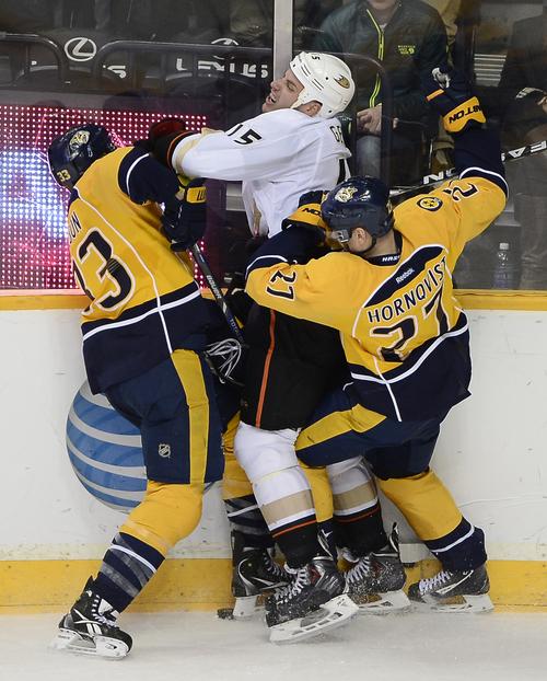 Nashville Predators forward Colin Wilson (33) and Patric Hornqvist (27), of Sweden, check Anaheim Ducks center Ryan Getzlaf (15) into the boards in the third period of an NHL hockey game on Saturday, Feb. 8, 2014, in Nashville, Tenn. The Ducks won 5-2. (AP Photo/Mark Zaleski)