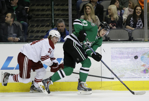 Phoenix Coyotes' Tim Kennedy (34) and Dallas Stars' Valeri Nichushkin (43) chase after a loose puck in the second period of an NHL hockey game, Saturday, Feb. 8, 2014, in Dallas. (AP Photo/Tony Gutierrez)