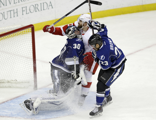 Detroit Red Wings left wing Henrik Zetterberg (40) runs into Tampa Bay Lightning goalie Ben Bishop (30) as right wing J.T. Brown (23) defends during the third period of an NHL hockey game Saturday, Feb. 8, 2014, in Tampa, Fla. The Lightning won the game 4-2. (AP Photo/Chris O'Meara)