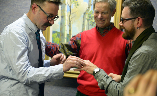 Keith Johnson     The Salt Lake Tribune Mark Hofeling, left, exchanges rings with new husband Jesse Walker while being married by Salt Lake City Mayor Ralph Becker outside the Salt Lake County Clerk'sOoffice, Friday, December 20, 2013. A federal judge in Utah Friday struck down the state's ban on same-sex marriage, saying the law violates the U.S. Constitution's guarantees of equal protection and due process.
