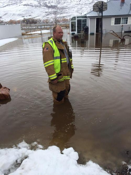 (Courtesy North Summit Fire District )  North Summit Fire District Capt. Daniel Hennefer surveys the flooding in Coalville Sunday afternoon, Feb. 9, 2014.
