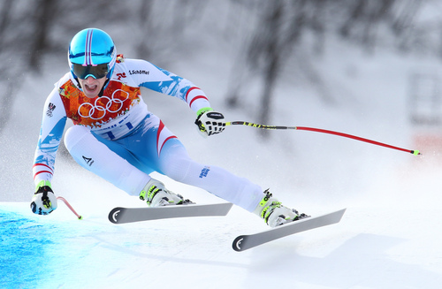 Austria's Matthias Mayer makes a turn in the men's downhill on his way to winning a gold medal at the Sochi 2014 Winter Olympics, Sunday, Feb. 9, 2014, in Krasnaya Polyana, Russia. (AP Photo/Alessandro Trovati)