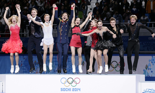 The Russian team jump onto the podium during the flower ceremony after placing first in the team figure skating competition at the Iceberg Skating Palace during the 2014 Winter Olympics, Sunday, Feb. 9, 2014, in Sochi, Russia. (AP Photo/Bernat Armangue)
