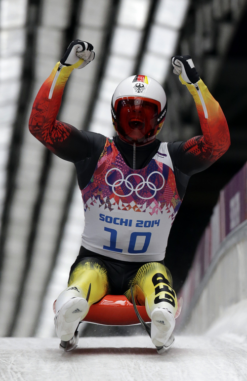 Felix Loch of Germany celebrates as he crosses the finish area to win the gold medal during the men's singles luge final at the 2014 Winter Olympics, Sunday, Feb. 9, 2014, in Krasnaya Polyana, Russia. (AP Photo/Michael Sohn)