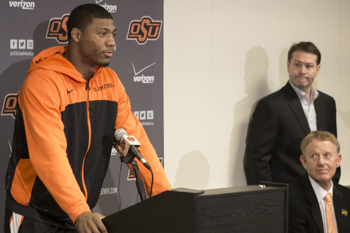 This photo provided by Oklahoma State University Athletics shows Oklahoma State basketball player Marcus Smart, left, addressing the media at a news conference in Stillwater, Okla., Sunday, Feb. 9, 2014, in regard to an altercation during an NCAA college basketball game the day before. Smart was suspended three games by the Big 12 for shoving a fan. Oklahoma State athletic director Mike Holder, bottom right, and Oklahoma State basketball coach Travis Ford look on. (AP Photo/Oklahoma State University Athletics, Bruce Waterfield)