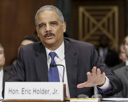 FILE - In this Jan. 29, 2014 file photo, Attorney General Eric Holder testifies on Capitol Hill in Washington. Holder called on a group of states Tuesday to restore voting rights to ex-felons, part of a push to fix what he sees as flaws in the criminal justice system that have a disparate impact on racial minorities.  (AP Photo/J. Scott Applewhite, File)