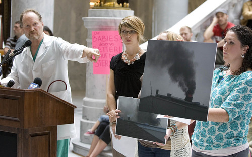 Paul Fraughton  |   Tribune file photo  Dr. Brain Moench points to a photo held by Sarah Sargent showing an emergency bypass event at the Stericycle medical waste incinerator in North Salt Lake. Clean-air advocates joined other concerned citizens at a rally in the Capitol rotunda last month to voice their demand that the incinerator be shut down.