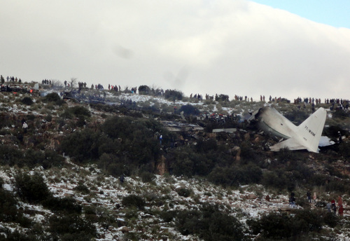 People look at the wreckage of Algerian military transport plane after it slammed into a mountain in the country's rugged eastern region, Tuesday, Feb. 11, 2014. A civil defense official said 102 people on board were killed but one person managed to survive. The U.S.-built C-130 Hercules transport crashed about noon near the town of Ain Kercha, 50 kilometers (30 miles) southeast of Constantine, the main city in eastern Algeria. ( AP Photo/ Mohamed Ali)