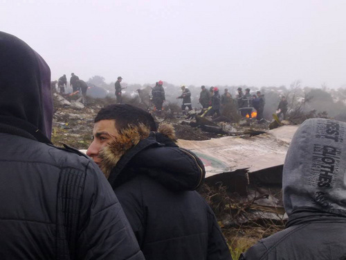 People watch rescue workers working at the wreckage of an Algerian military transport aircraft after it slammed into a mountain in the country's rugged eastern region, Tuesday, Feb. 11, 2014. A civil defense official said 102 people on board were killed but one person managed to survive. The U.S.-built C-130 Hercules transport crashed about noon near the town of Ain Kercha, 50 kilometers (30 miles) southeast of Constantine, the main city in eastern Algeria. ( AP Photo/ Mohamed Ali)