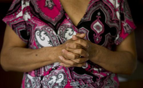 In this Feb. 5, 2014, photo, Maria Gonzalez clasps her hands during an interview with The Associated Press inside his home in Yautepec, Mexico. In 2012, her son Cesar, a 33-year-old architect and engineer, was kidnapped as he drove through Cuernavaca to visit his family in Yautepec. The family got together $10,000 and left it in packets of $2,000 in a cereal box in Cuernavaca. Five days later he was found dead in the trunk of his car. (AP Photo/Eduardo Verdugo)