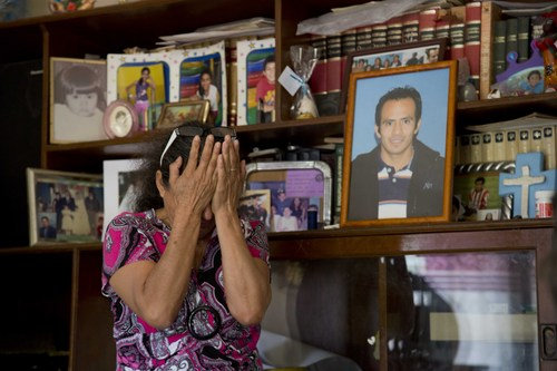 In this Feb. 5, 2014, photo, Maria Gonzalez, weeps next to a portrait of her son Cesar, during an interview with The Associated Press inside her home in Yautepec, Mexico. In 2012. Cesar, a 33-year-old architect and engineer, was kidnapped as he drove through Cuernavaca to visit his family in Yautepec. The family got together $10,000 and left it in packets of $2,000 in a cereal box in Cuernavaca. Five days later he was found dead in the trunk of his car. (AP Photo/Eduardo Verdugo)