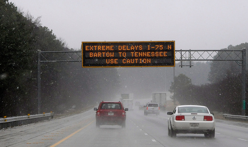 """A Georgia transportation sign warns motorists on Interstate 75 on Tuesday, Feb. 11, 2014, in Kennesaw, Ga., about 20 miles north of metro Atlanta.  A winter snow storm is  blowing into Georgia in what the National Weather Service predicted to be """"an event of historical proportions.""""  (AP Photo/David Tulis)"""