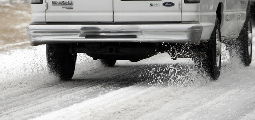 A van kicks up snow and ice as it travels on I-65 North on Tuesday, Feb. 11, 2014, in Cullman, Ala. A winter storm dropped several inches of snow and ice in North Alabama overnight and more is expected. (AP Photo/Butch Dill)