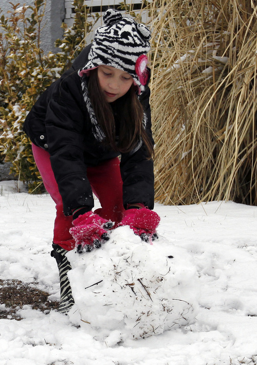 Adrianne Lynn DeBruhl, of Cullman, rolls up a snow ball to put on her snowman on Tuesday, Feb. 11, 2014, in Cullman, Ala. A winter storm dropped several inches of snow on North Alabama overnight and more is expected. (AP Photo/Butch Dill)