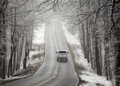 A vehicle travels on Stevens Rd. on Tuesday, Feb. 11, 2014, in Greenville, S.C. Snow and icy conditions were expected to continue in the state through Wednesday. (AP Photo/Rainier Ehrhardt)
