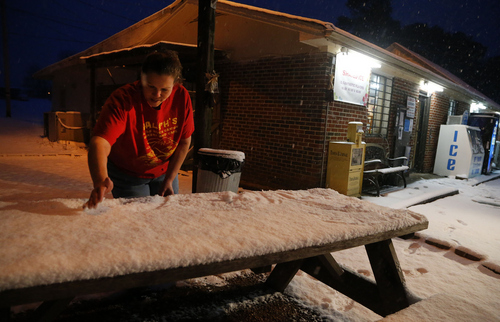 Employee Brandy Aaron scrapes snow to make snow cream at Ralph's Lil River Canyon Grocery and Grill as snow falls, Tuesday, Feb. 11, 2014, in Fort Payne, Ala. Residents were waking up to a heavy blanket of snowfall that was expected to continue throughout the morning. (AP Photo/Hal Yeager)