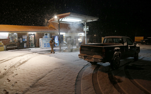 Allen Johnson returns to his truck after getting coffee at Ralph's Lil River Canyon Grocery and Grill as snow falls, Tuesday, Feb. 11, 2014, in Fort Payne, Ala. Residents were waking up to a heavy blanket of snowfall that was expected to continue throughout the morning. (AP Photo/Hal Yeager)