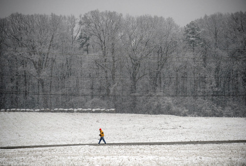 John Szeto walks along Blacks Drive on Tuesday, Feb. 11, 2014, in Greenville, S.C. Residents woke to a  snow that was expected to continue throughout the morning hours. (AP Photo/Rainier Ehrhardt)