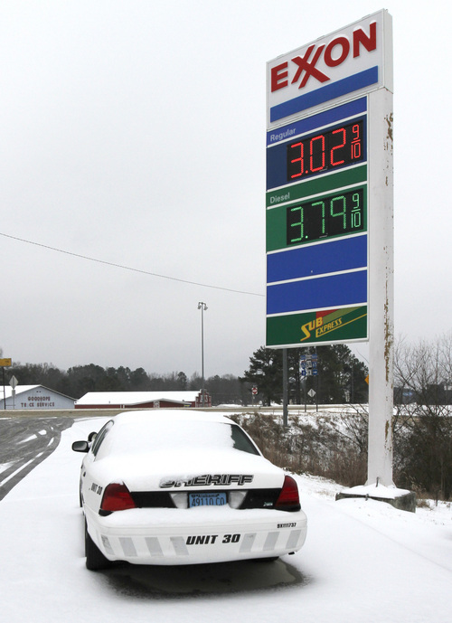 A Sheriff's car is covered in snow at a gas station on Tuesday, Feb. 11, 2014, in Cullman, Ala.  A winter storm dropped several inches of snow and ice in North Alabama overnight and more is expected. (AP Photo/Butch Dill)