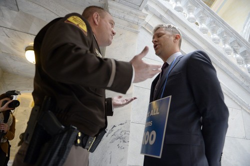 Francisco Kjolseth  |  The Salt Lake Tribune Highway patrol trooper Travis Trotta argues with LGBT activist Troy Williams after removing him from the front door of the governor's office at the Capitol on Monday, Feb. 9, 2014, as Williams demands that anti-discrimination bill SB100 be heard.