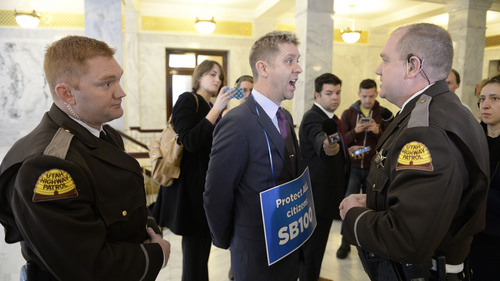 "Francisco Kjolseth  |  The Salt Lake Tribune LGBT activists Troy Williams asks ""Am I being arrested?"" as he is moved away from his group having a stand-in blocking the entrance to the governor's office at the Capitol on Monday, Feb. 9, 2014. The protesters are pushing to have anti-discrimination bill SB100 be heard."