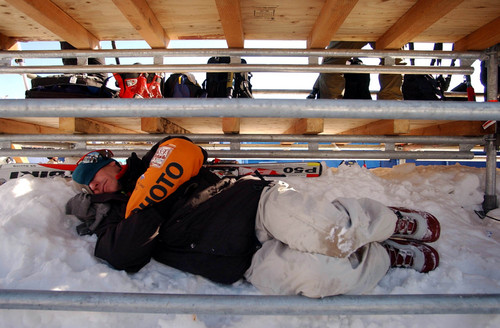 Following a weather delay from the day before of the women's downhill at Snowbasin, Tom Moran a photographer with Sports Illustrated Daily catches up on some sleep under the photo bleachers while waiting out more that a two hour delay on Tuesday.  02/11/2002, 11:02:53 PM