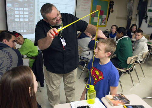 Keith Johnson | The Salt Lake Tribune/POOL  Teacher Rob Lake measures Jeffery Carlton during the introduction to statics class at Kearns High School, February 5, 2014 in Kearns, Utah. Students entered their height information into a Texas Instruments wireless calculator that transmits its data onto the screen behind Mr. Lake. for all to see. The Utah Legislature is looking into infusing millions of dollars for technology in Utah classrooms. Kearns High received a $1 million grant 3 years ago, allowing every student to get an iPod touch to help in the classroom. The results were mixed.