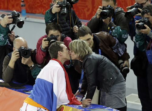 Photographers shoot Stefan Groothuis of the Netherlands being congratulated after winning the gold in the men's 1,000-meter speedskating race at the Adler Arena Skating Center at the 2014 Winter Olympics in Sochi, Russia, Wednesday, Feb. 12, 2014. (AP Photo/Patrick Semansky)
