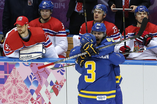 Sweden defenseman Erik Karlsson (65) celebrates with Czech Republic defenseman Radko Gudas after scoring a goal against the the Czech Republic in the first period of a men's ice hockey game at the 2014 Winter Olympics, Wednesday, Feb. 12, 2014, in Sochi, Russia. (AP Photo/Julio Cortez)