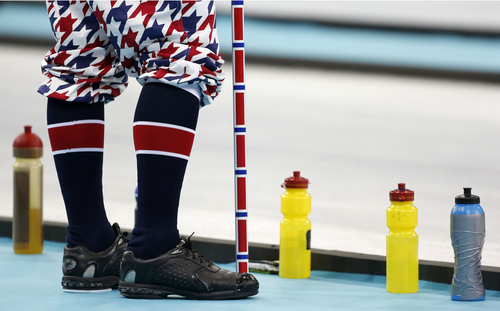 A Norwegian curler stands next to water bottles during men's curling competition against Germany at the 2014 Winter Olympics, Wednesday, Feb. 12, 2014, in Sochi, Russia. (AP Photo/Robert F. Bukaty)