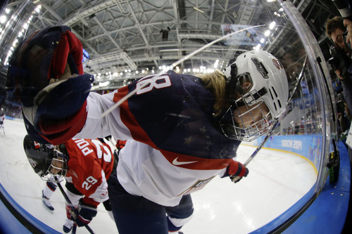 Lyndsey Fry of the United States is pushed up agaisnt the glass as she fights for control of the puck with Marie-Philip Poulin of Canada during the first period of the 2014 Winter Olympics women's ice hockey game at Shayba Arena, Wednesday, Feb. 12, 2014, in Sochi, Russia. (AP Photo/Matt Slocum)
