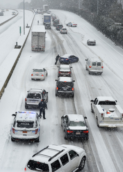 Traffic along Independence Boulevard near Hawthorne Lane crawls along the slick roadway as a winter storm hits   Wednesday, Feb. 12, 2014, in Charlotte, N.C. (AP Photo/The Charlotte Observer, Davie Hinshaw) MAGS OUT; TV OUT; NEWSPAPER INTERNET ONLY